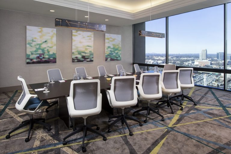 Full view of the Sky Boardroom table at Crowne Plaza Atlanta Midtown with a view of the Atlanta skyline.