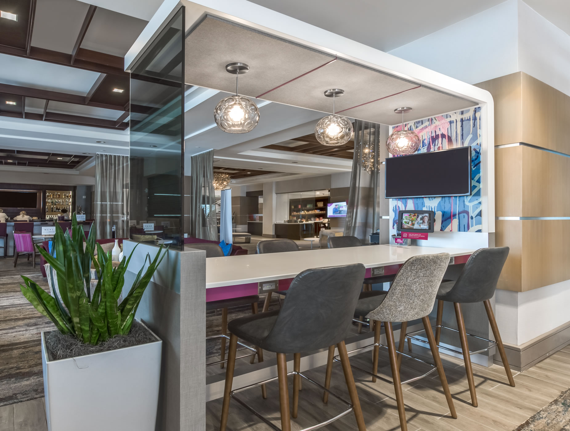Hotel lobby and lounge area featuring bar chairs and flat screen TVs.