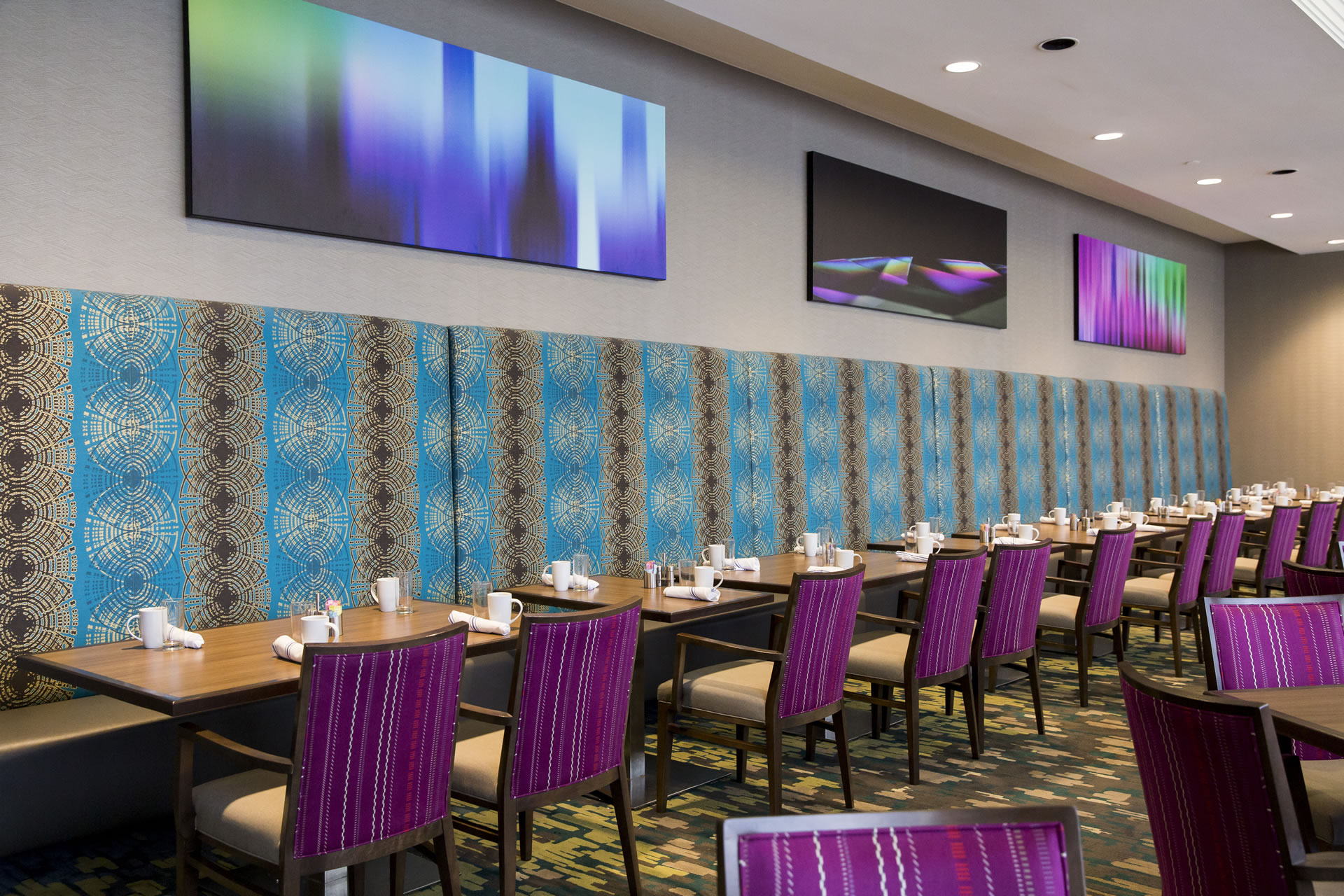 A row of dining tables and purple chairs at Next restaurant at Crowne Plaza Atlanta Midtown.