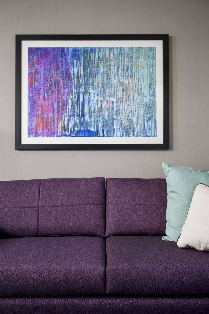 Close up of purple couch, pillows, and artwork hanging on the wall above the furniture at Crowne Plaza Atlanta Midtown.