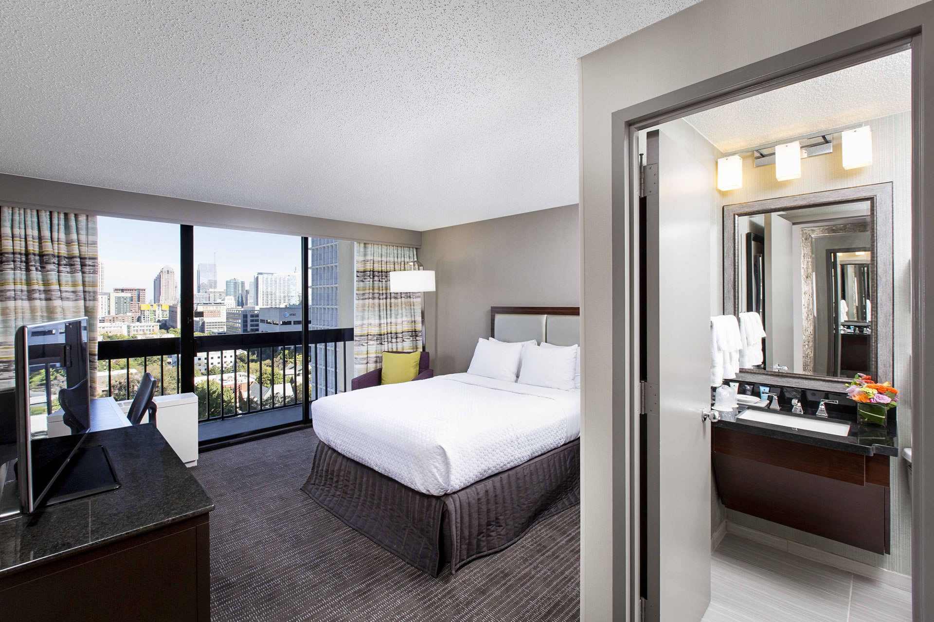 Guest room with one queen bed and a view of the Atlanta skyline at Crowne Plaza Atlanta Midtown.
