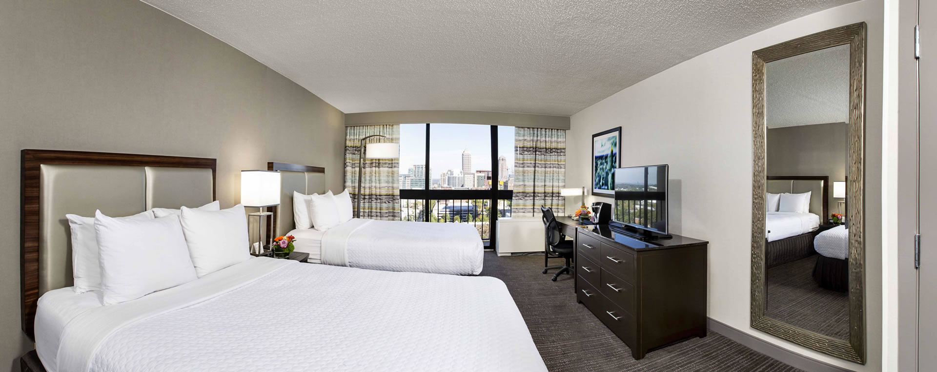 Guest room with two queen beds and a view of the Atlanta skyline at Crowne Plaza Atlanta Midtown.