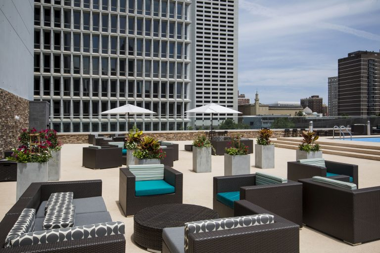 Rooftop pool deck of the Crowne Plaza Atlanta Midtown with outdoor lounge chairs and patio umbrellas.