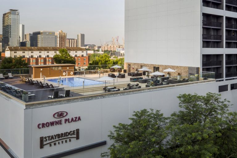 View of rooftop pool deck and the Atlanta skyline at the Crowne Plaza Atlanta Midtown.