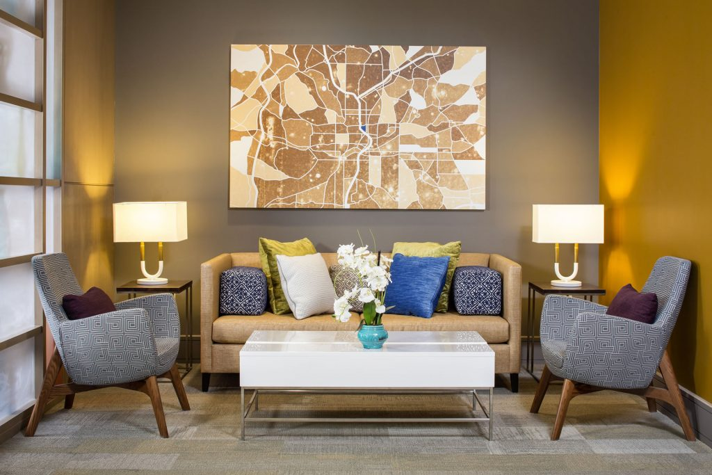 A couch and coffee table with two chairs and an abstract map of Atlanta hanging on the wall above the furniture.