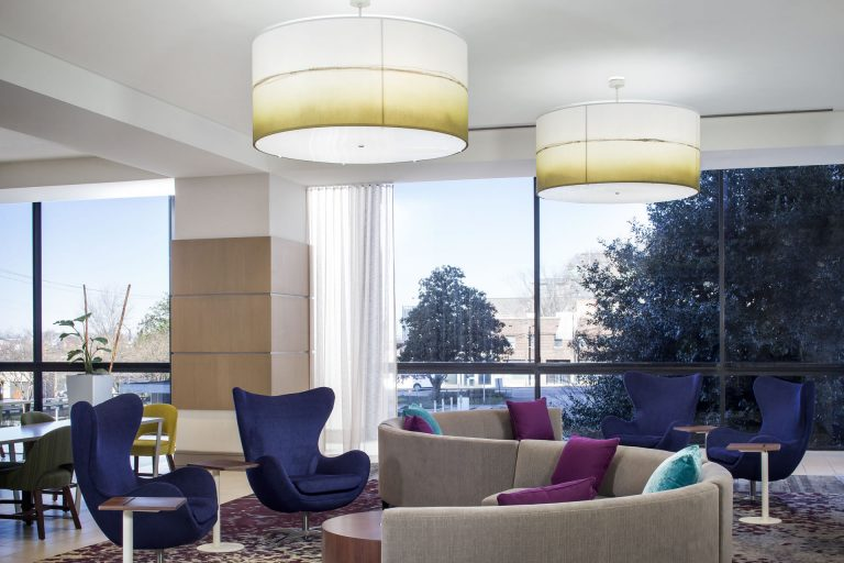 Blue lounge chairs and curvy couches in the lounge of the Crowne Plaza Atlanta Midtown.