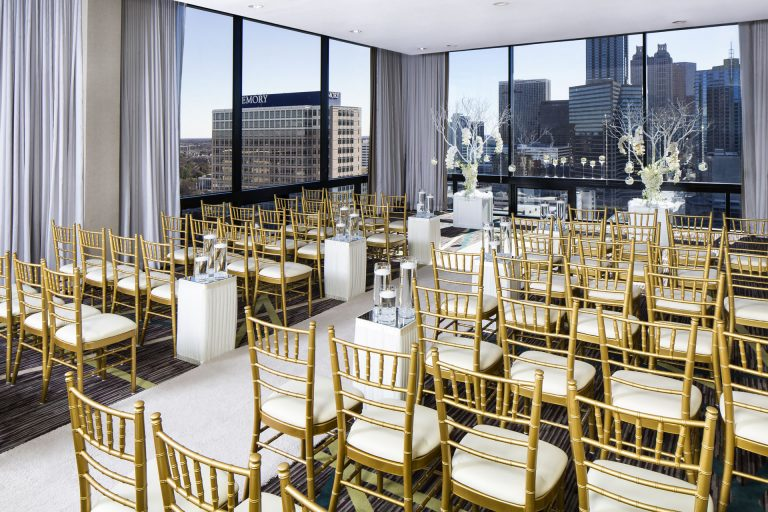 Wedding ceremony aisle and guest chairs in the SKY Room East at the Crowne Plaza Atlanta Midtown, overlooking the Atlanta skyline.