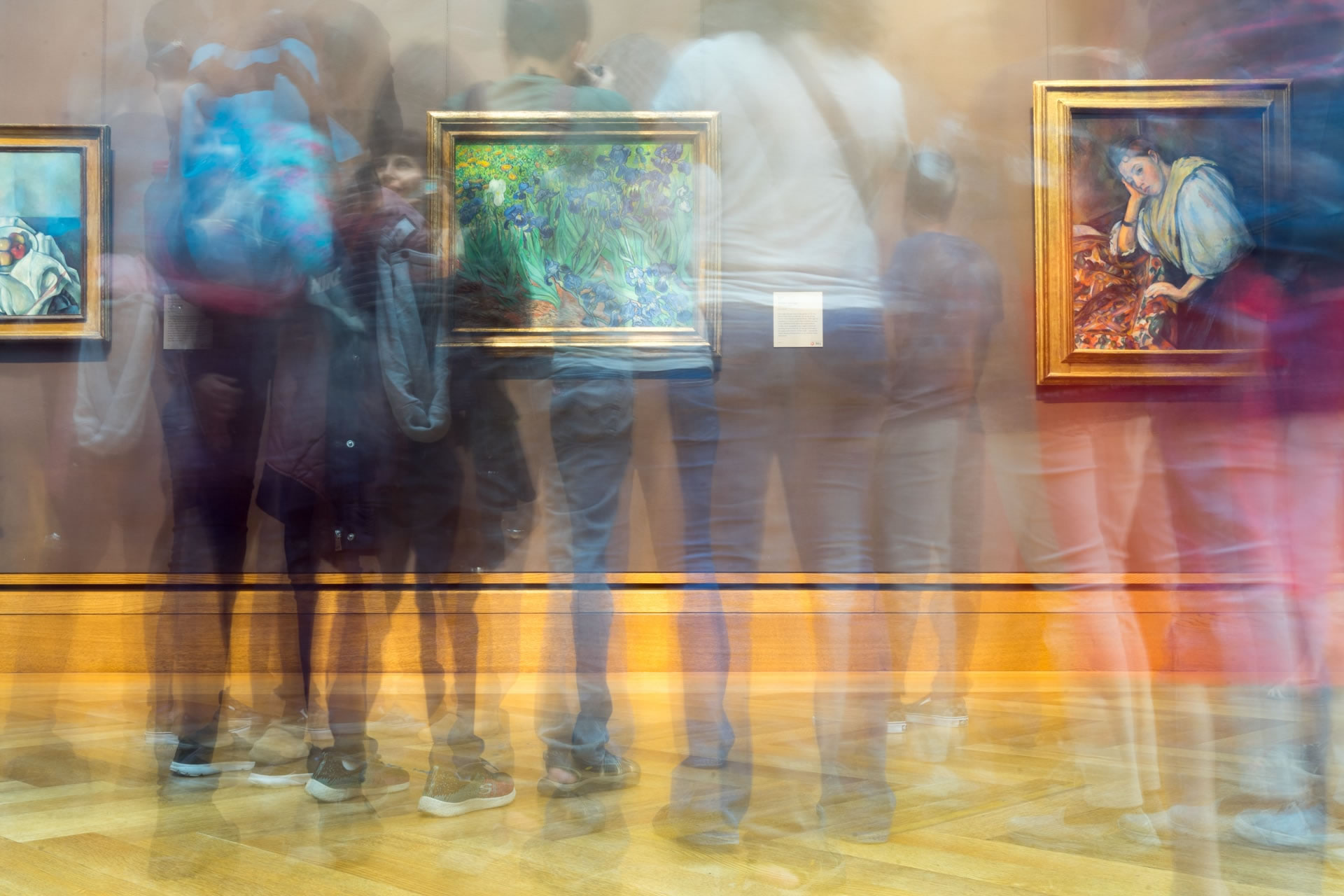 Paintings in an art gallery, photographed using a long exposure to show the ghostly movements of patrons.