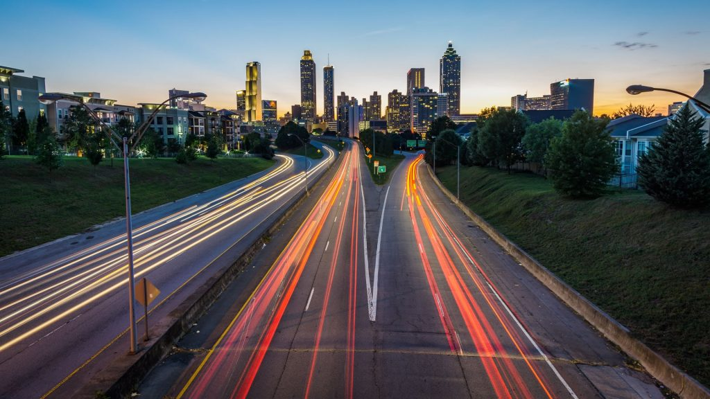 Sunset on the Atlanta skyline with a blur of car headlights and taillights along the highway heading heading in and out of the city.