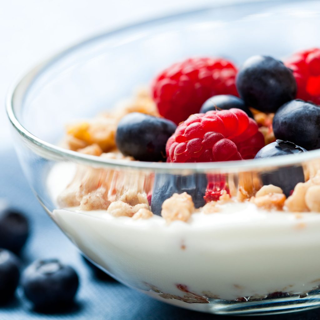 A close up of a bowl of yogurt topped with granola, blueberries, and raspberries.