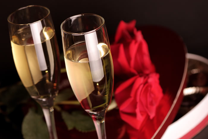 Two glasses of champagne and two roses on a table.