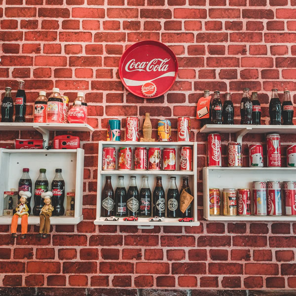 A brick wall adorned with various old Coca-Cola bottles and cans