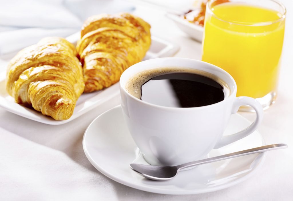 Cup of coffee, croissants, and a glass of orange juice.