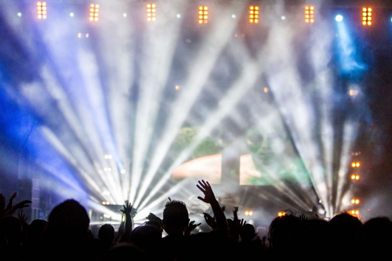 Silhouette of concert-goers in front of a smoke-filled stage with stage lights.