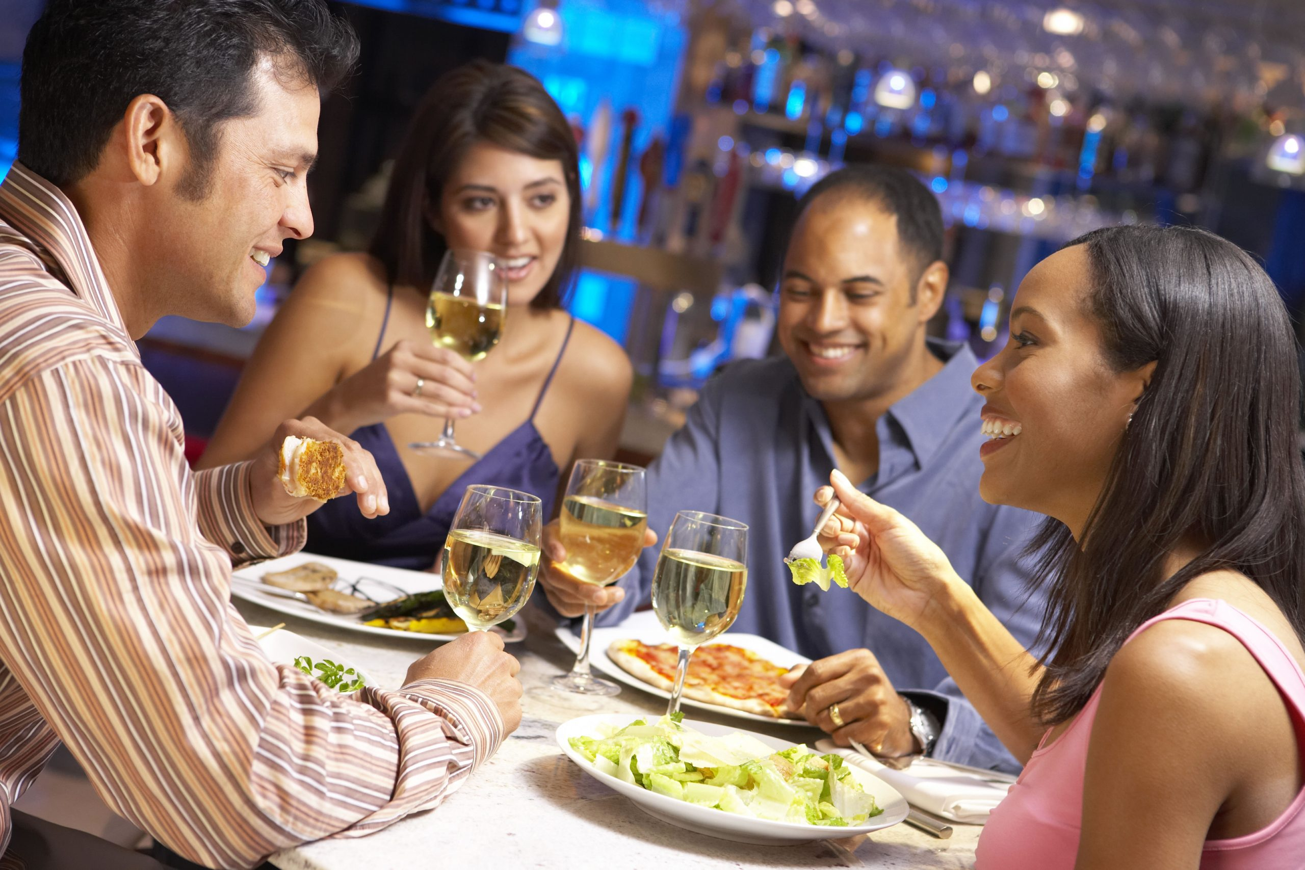 Two couples enjoying dinner and wine together at a restaurant.