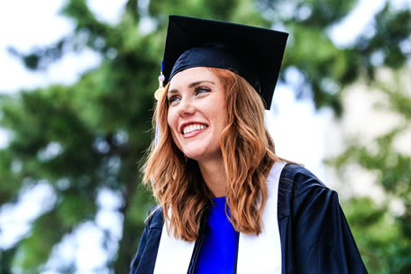 A smiling woman in her graduation cap and gown