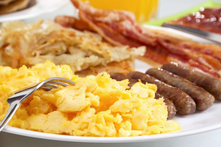 Close up of a plate of breakfast consisting of scrambled eggs, bacon, hash browns, and sausage.