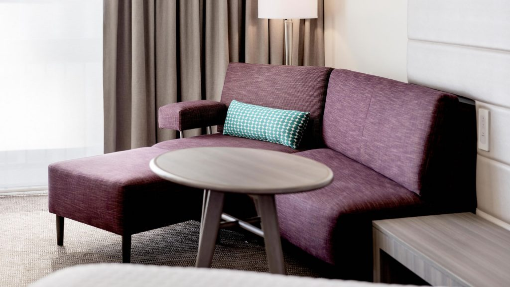Chaise lounge and table in a king guest room at Crowne Plaza Atlanta Midtown.
