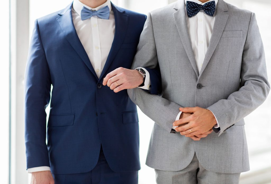 Two men in suits and bow ties standing arm in arm for their wedding.