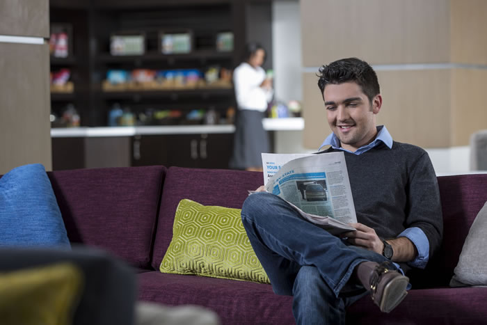 A smiling man reading a newspaper in the lobby lounge of the Crowne Plaza Atlanta Midtown.