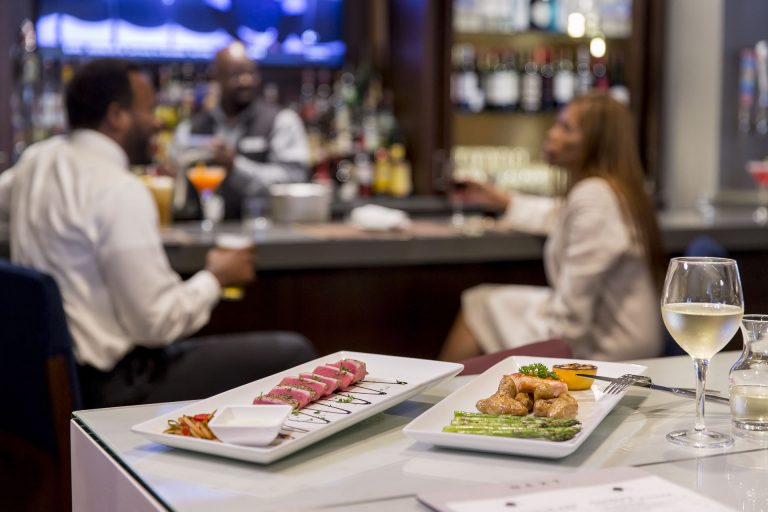 A close up of a glass of wine and two entrees at Next restaurant in Crowne Plaza Atlanta Midtown: ahi tuna and fish, potatoes, and asparagus. Guests are enjoying drinks at the bar in the background.