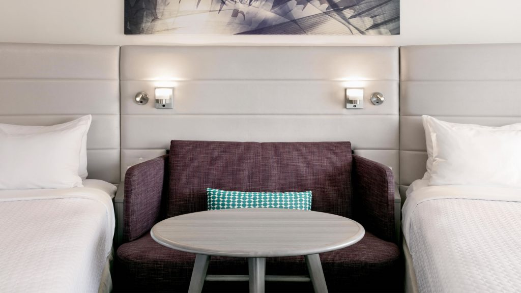 Love seat and table between two queen beds at Crowne Plaza Atlanta Midtown.