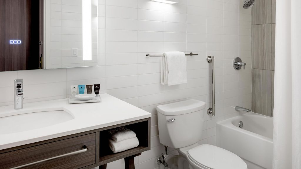 Toilet, sink, and shower/bathtub in the bathroom at the Crowne Plaza Atlanta Midtown with ADA shower grip bar.