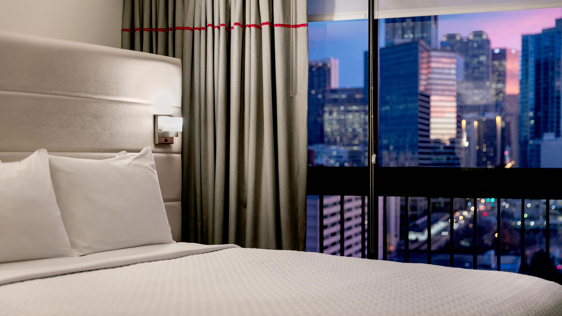 Close up of bed and pillows at the Crowne Plaza Atlanta Midtown with the city skyline out the window in the background.