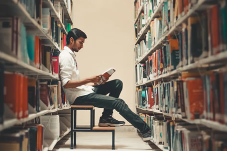 Young male student sitting on a stool between two library shelves filled with books.