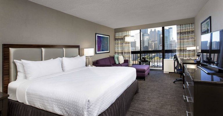 Guest room with one king bed and a view of the Atlanta skyline at Crowne Plaza Atlanta Midtown.