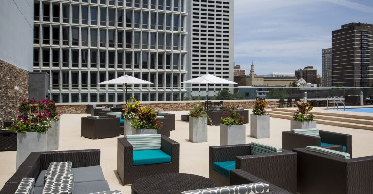 Rooftop pool deck at Crowne Plaza Atlanta Midtown with lounge chairs and umbrellas.