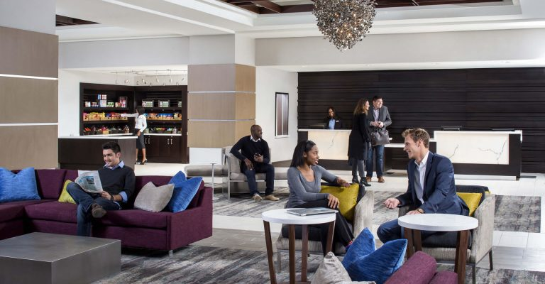 Guests relaxing near the lounge, front desk, and The Market at Crowne Plaza Atlanta Midtown.
